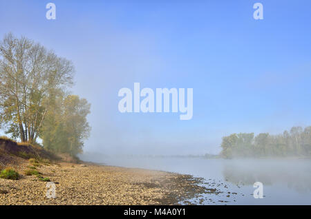 Foggy autumn morning on the bank of the river - Stock Photo