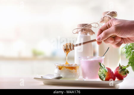 Dairy in white kitchen and hand making honey in curd with strawberry yogurt, fruit and bottles milk Front view. - Stock Photo