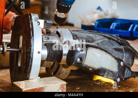 Processing of a furniture part by a machine for polishing a tree. the grinding machine on a board, selective focus. - Stock Photo