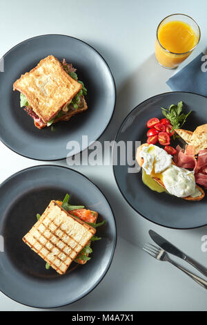 sandwiches on plates, egg with tomatoes and fresh juice - Stock Photo