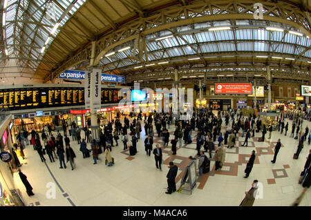 Extreme wide angle view of Kings Cross railway Station concourse filled with passengers waiting for their trains, - Stock Photo