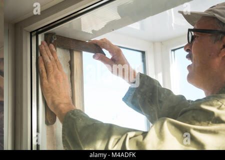 Carpenter makes measurements when installing the window - Stock Photo