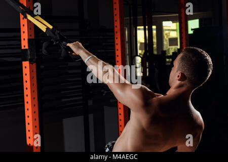 TRX training. Crossfit instructor at the gym doing TRX Excersise. - Stock Photo