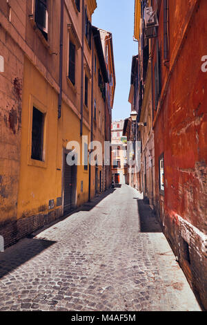 Narrow Italian street with colorful houses without people on a sunny day Rome, Italy - Stock Photo