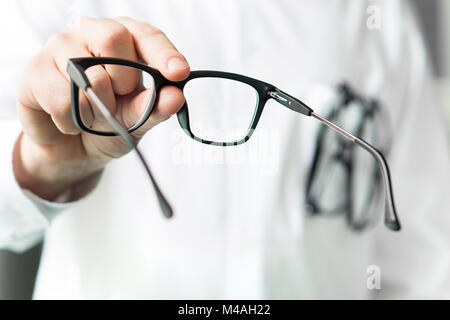 Optician giving new glasses to customer for testing and trying. Eye doctor showing patient lenses. Professional - Stock Photo
