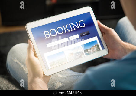 Booking app or website on tablet screen. Man searching hotel and flights for holiday and vacation with travel application. - Stock Photo