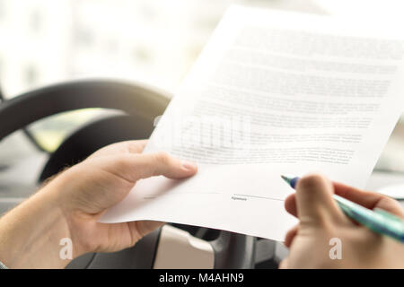 Signing lease or buying new or used car. Man about to write autograph to legal document. Motor vehicle insurance - Stock Photo