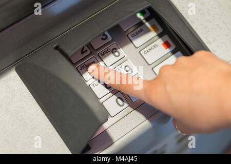 Woman entering her pin code number to atm machine. Money and cash withdrawal concept. Hand on buttons and keypad. - Stock Photo