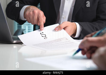 Lawyer giving legal advice to a client in office. People in law firm having meeting. Attorney pointing a section sign on paper.