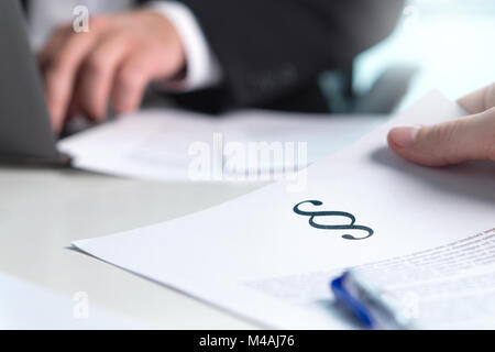 People in law firm having meeting. Lawyer giving legal advice to a client in office. Man holding a paper with a section sign.