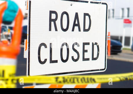 Road closed sign and block in a busy city street in the middle of traffic. Roadblock in a highway. - Stock Photo