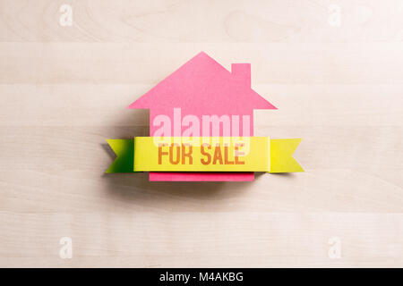 House for sale. Real estate business concept. Selling and buying home. Cottage made from cardboard paper on wooden - Stock Photo