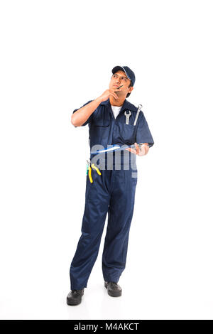 Indian happy auto mechanic in blue suit and cap holding spanner tool in action, isolated over white background - Stock Photo