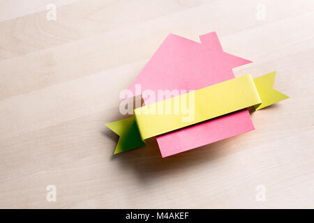 House for sale. Cottage made from cardboard paper on wooden table. House warming party template. Empty blank ribbon - Stock Photo