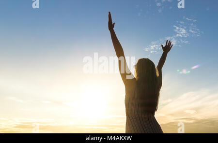 Brave happy young woman raising hands up in the air and open arms to sky. Enjoying life. Sunny healthy lifestyle - Stock Photo