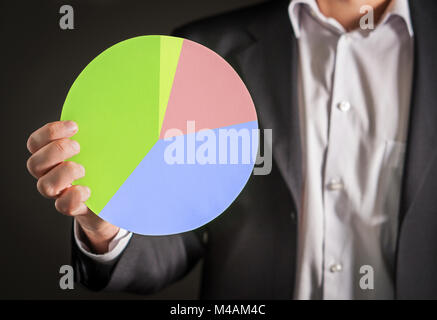 Business man holding a pie chart made from cardboard paper. Visual demonstration of finance statistics and market - Stock Photo