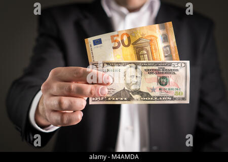 Dollar vs euro. Business man in suit holding 50 banknote and bill in both currency in hand. Exchange rate, world - Stock Photo