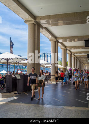 People walking by shops, bars and restaurants on the east side of Circular Quay, Sydney, New South Wales, Australia - Stock Photo