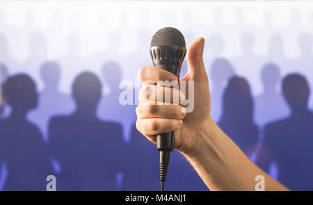 Hand holding microphone and showing thumbs up in front of a crowd of silhouette people. Public speaking and giving - Stock Photo