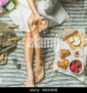 Woman in dress sitting with wine and snacks, square crop - Stock Photo