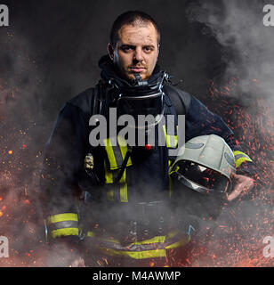 A firefighter dressed in a uniform in a studio. - Stock Photo