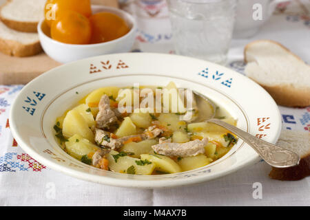 Stew or ror roast or soup with meat and potatoes, served with canned tomatoes and bread. Selective focus. - Stock Photo