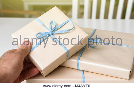 Man holding present gift box wrapped in paper - Stock Photo