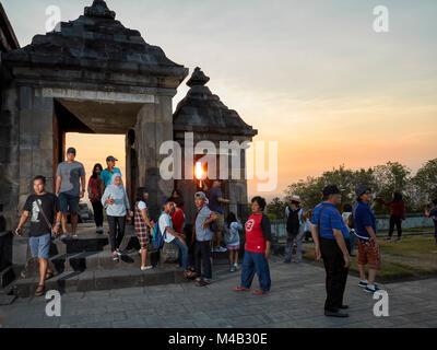 Tourists at the main gate of Ratu Boko Palace compound at sunset. Special Region of Yogyakarta, Java, Indonesia. - Stock Photo