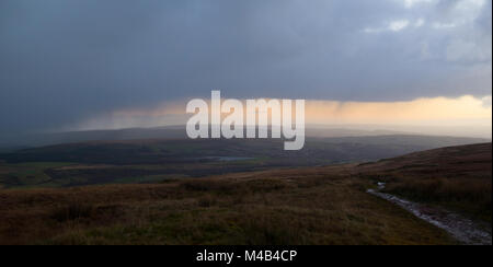 Looking from Winter Hill towards Bury and the Derbyshire Dales with wind turbines working under a stormy winter - Stock Photo