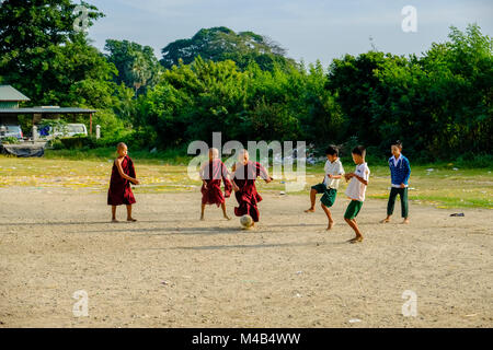 Young monks are playing football with the local boys - Stock Photo
