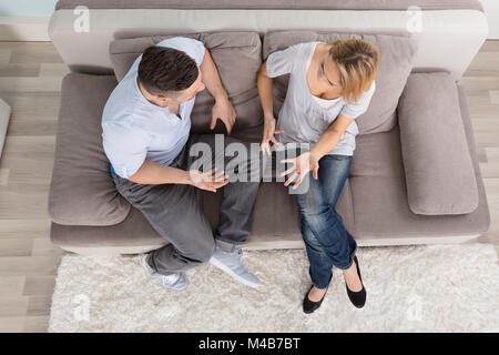 Overhead View Of A Couple Sitting On Couch Having Discussion At Home - Stock Photo