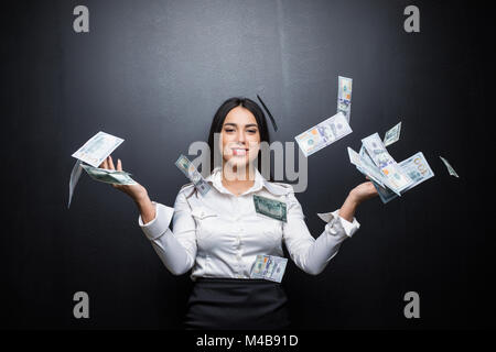 Happy business woman under a money rain made of dollars isolated on black background - Stock Photo