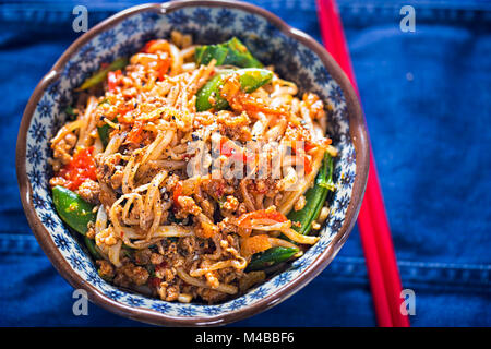 Sichuan spicy pork noodles with bean sprouts, sugar snap peas and oak choi - Stock Photo