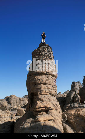 Algeria, Djanet. Sahara desert. National Park Tassili n'Ajjer. Photographer Frans Lemmens taking picture from rock. - Stock Photo
