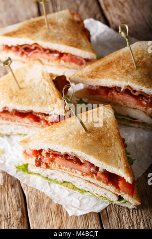 Club sandwich with turkey, bacon, cheese and vegetables close-up on the table. vertical - Stock Photo
