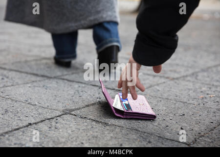 Close Of A Man Picking Up A Lost Purse On Street - Stock Photo