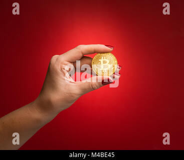 Holding golden bitcoin on red background, cryptocurrency concept - Stock Photo