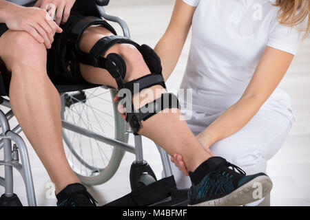 Female Physiotherapist Fixing Knee Braces On Man's Leg In A Clinic - Stock Photo
