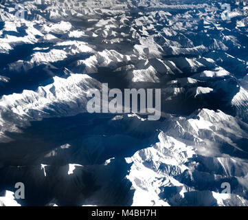 Aerial view over the rocky mountains from the airplane - Stock Photo