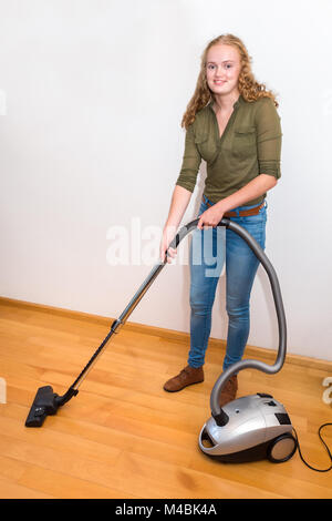 Young woman cleans floor with vacuum cleaner - Stock Photo