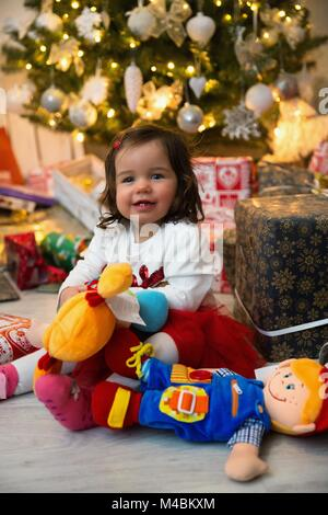 Baby while unpacking gifts at the Christmas tree - Stock Photo