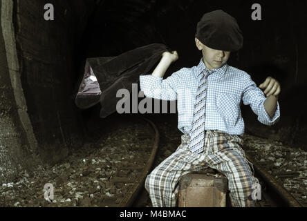 Child in vintage clothes sits on railway road - Stock Photo