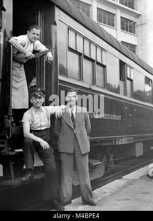 Personal poses in front of the restaurant wagon,cook,conductor and passenger,1940s,exact location unknown,Germany - Stock Photo
