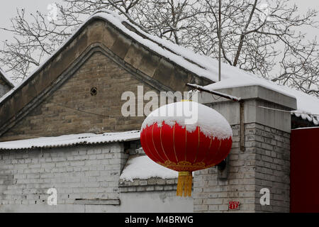 A red lantern at the entry of a house in Beijing for the Chinese New Year by a snowy day - Stock Photo