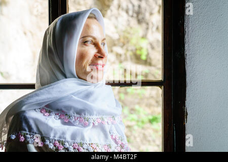 Portrait of a woman wearing traditional headscarf at a Dervish monastery in Bosnia - Stock Photo