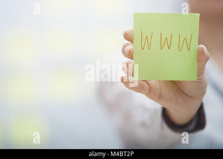 Hands holding sticky note with internet address - Stock Photo