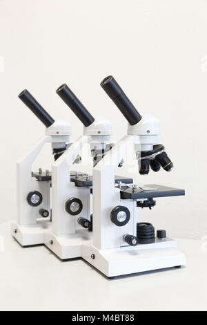 Three microscopes in a row isolated on background - Stock Photo