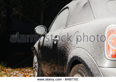 Convertible car parked in city covered with snow - Stock Photo