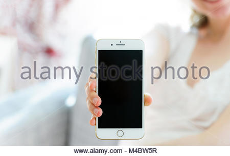 Woman presenting new luxury iPhone 7 Plus smartphone - Stock Photo