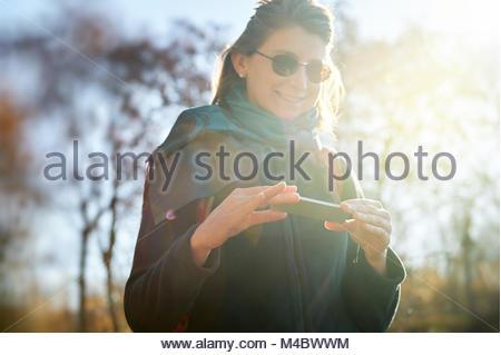 Smiling Woman using futuristic phone outdoor sun flare - Stock Photo